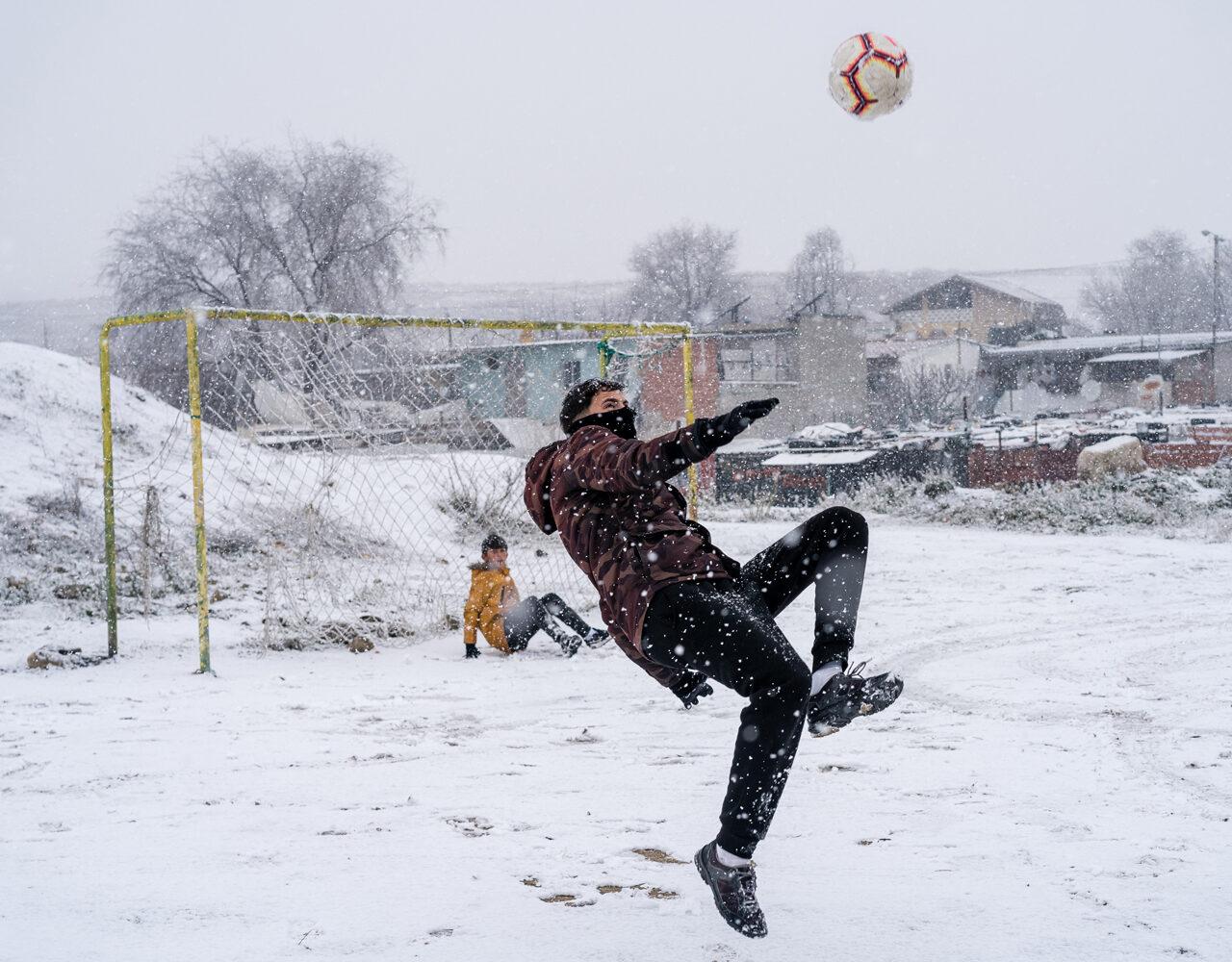 Vecinos de la Cañada Real Galiana juegan futbol durante la nevada.